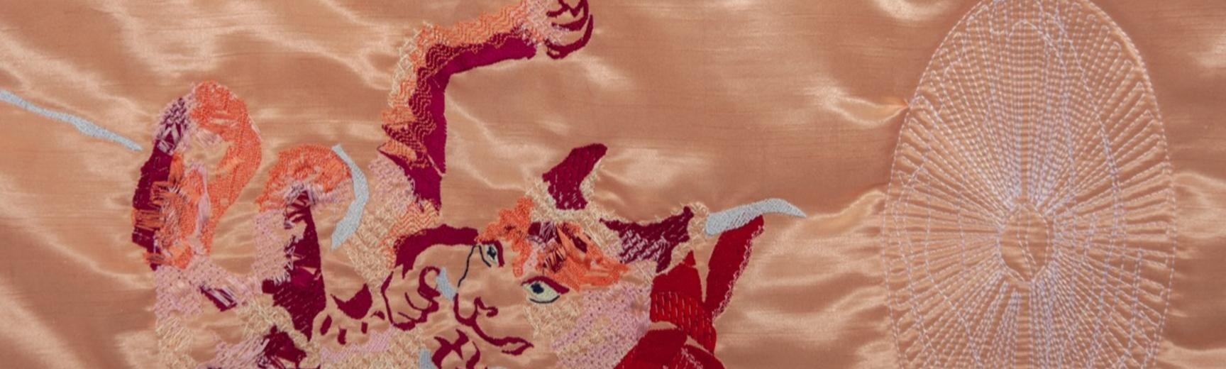 Close-up of a machine-embroidered cat on a satin quilt.