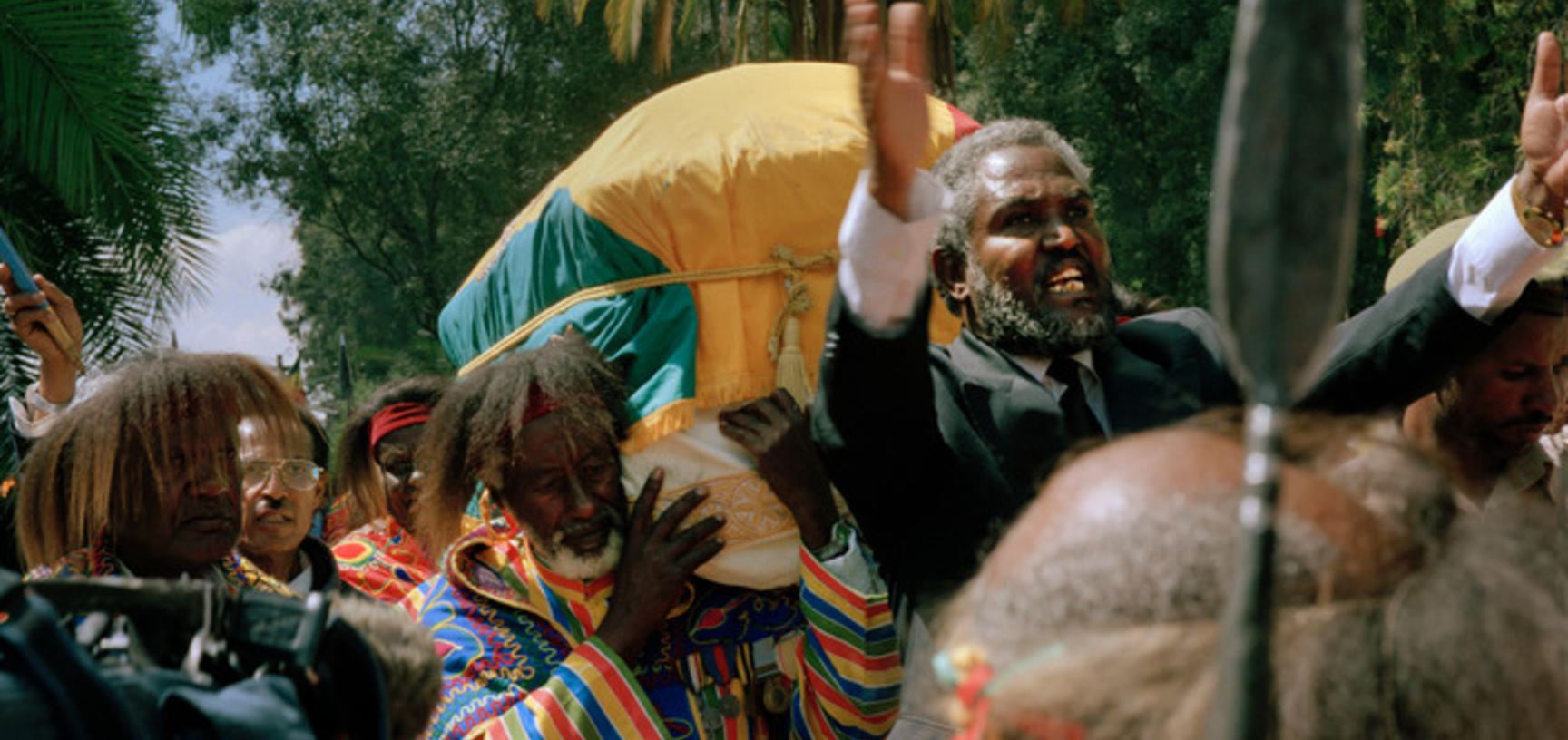 Veteran soldiers carry the Emperor's coffin towards Trinity Cathedral, as a man calls out praises. Addis Ababa, Ethiopia. Photograph by Peter Marlow. 2000.