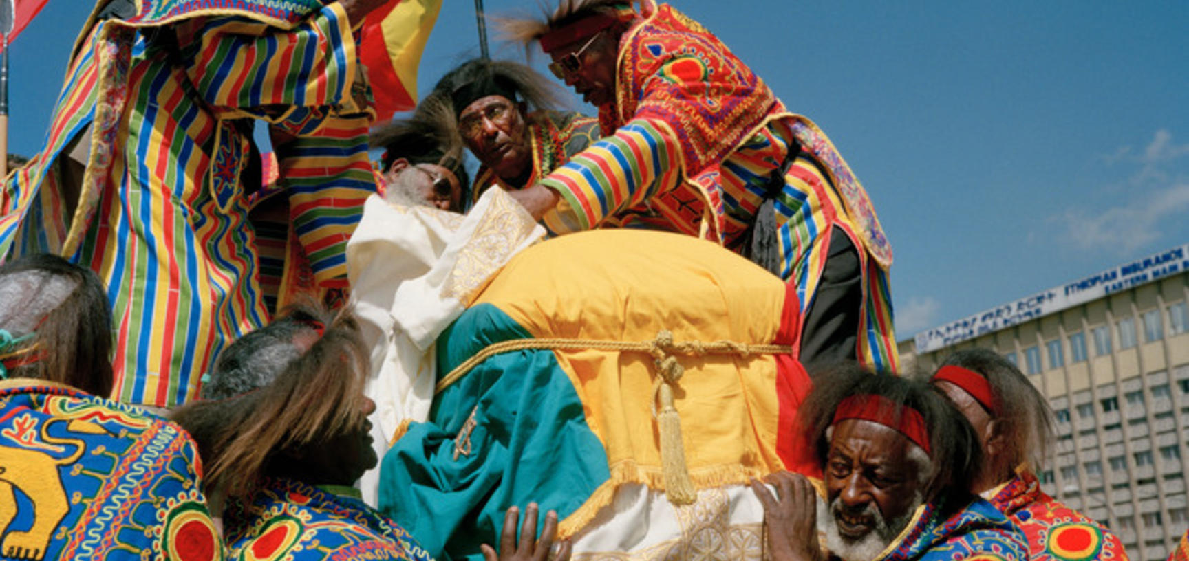 Veteran soldiers take Emperor Haile Selassie's coffin from the processional vehicle and onto their shoulders. Addis Ababa, Ethiopia. Photograph by Peter Marlow. 2000.