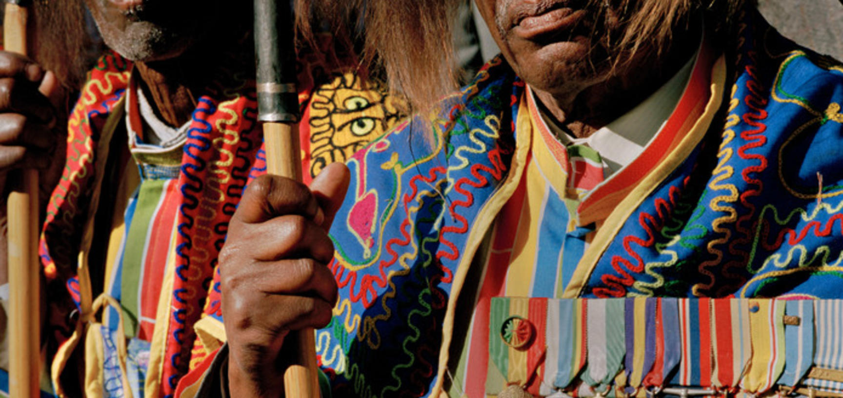 Veterans wearing lion's mane headdresses and military service medals forming a guard of honour for the Emperor's coffin on its way to Trinity Cathedral. Addis Ababa, Ethiopia. Photograph by Peter Marlow. 2000.