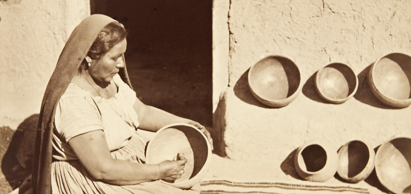 Woman polishing the inside of a large clay pot with a smooth pebble.
