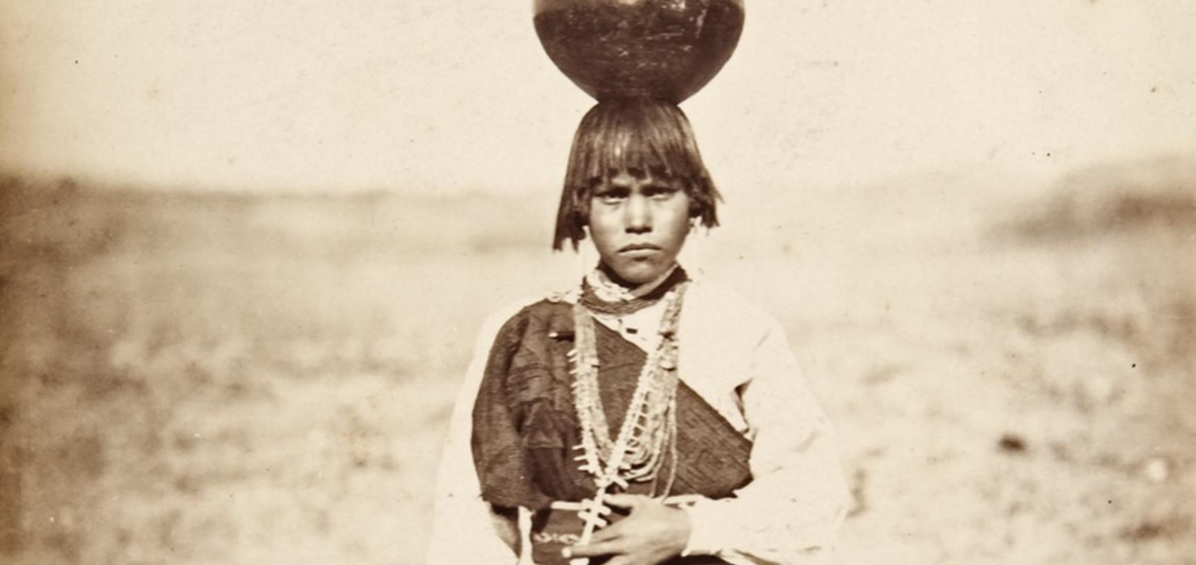 Pabla Tafolla, dressed in a woollen manta of local manufacture, carrying a blackware water jar on her head.