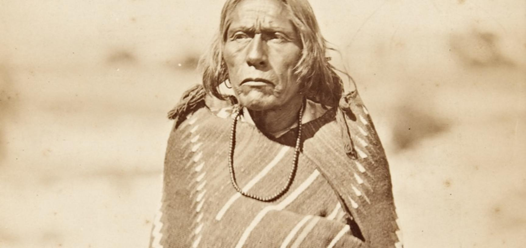 Portrait of the governor of San Juan Pueblo (present-day Ohkay Owingeh), standing, wrapped in a blanket.