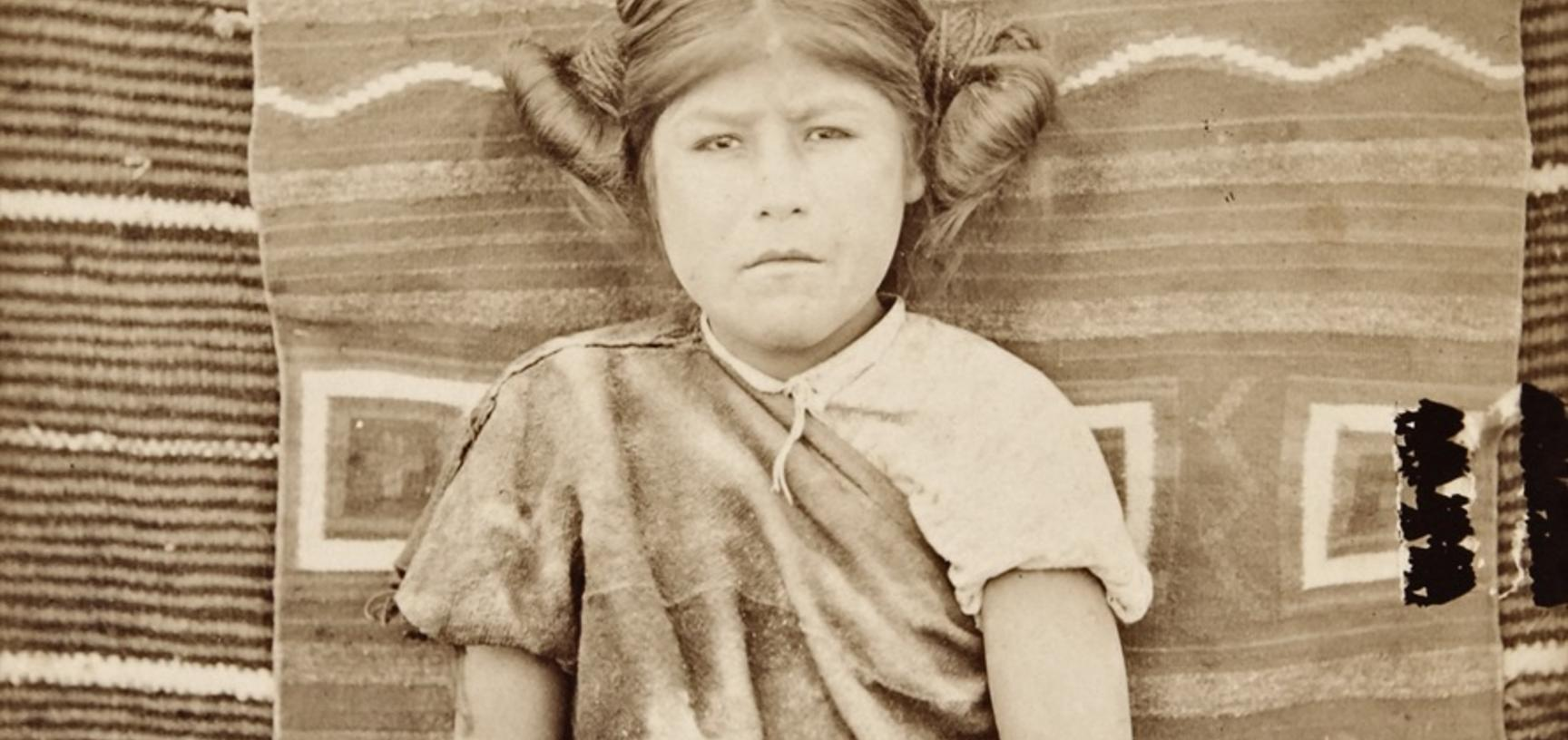 Portrait of a thirteen-year-old Hopi girl named 'Modisi', pictured sitting in front of a Navajo blanket.