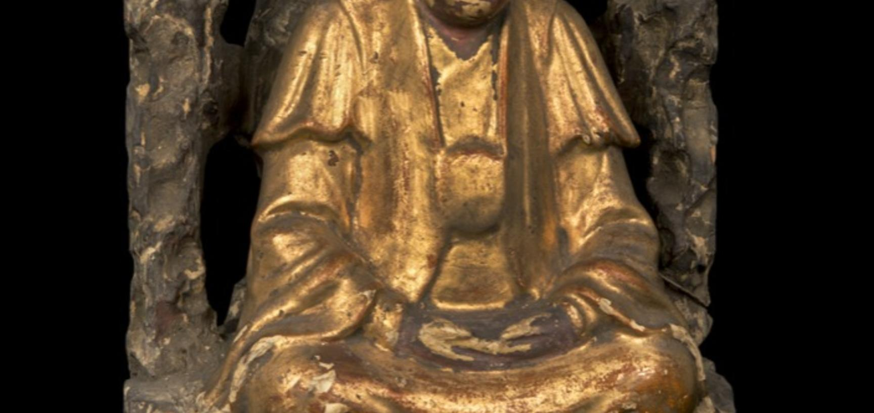 Wooden figure gilded in gold, seated under a bush.