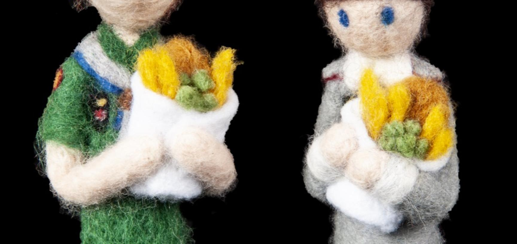 Two felted figures dressed in midwife uniforms and holding felted fish and chips.