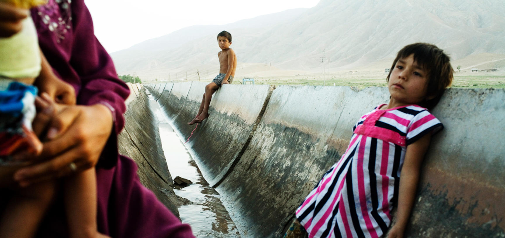 Children cool off in an irrigation canal that flows intermittently through their village. It is their only source of water. Akjar, Tajikistan. Photograph by Carolyn Drake. July 2008.