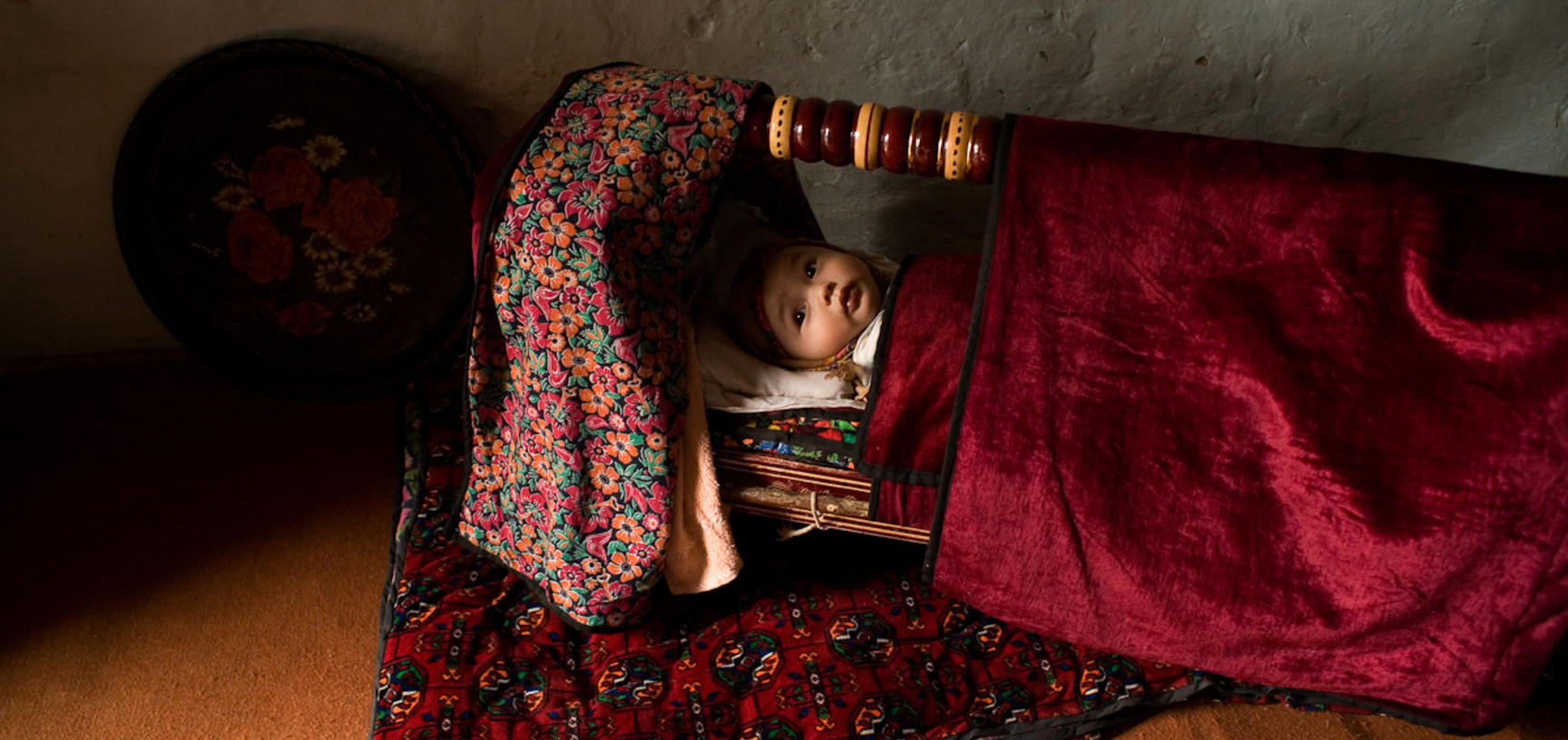 A baby in a crib on the floor of a house in the Ferghana Valley. Yaipan, Uzbekistan. Photograph by Carolyn Drake. March 2007.