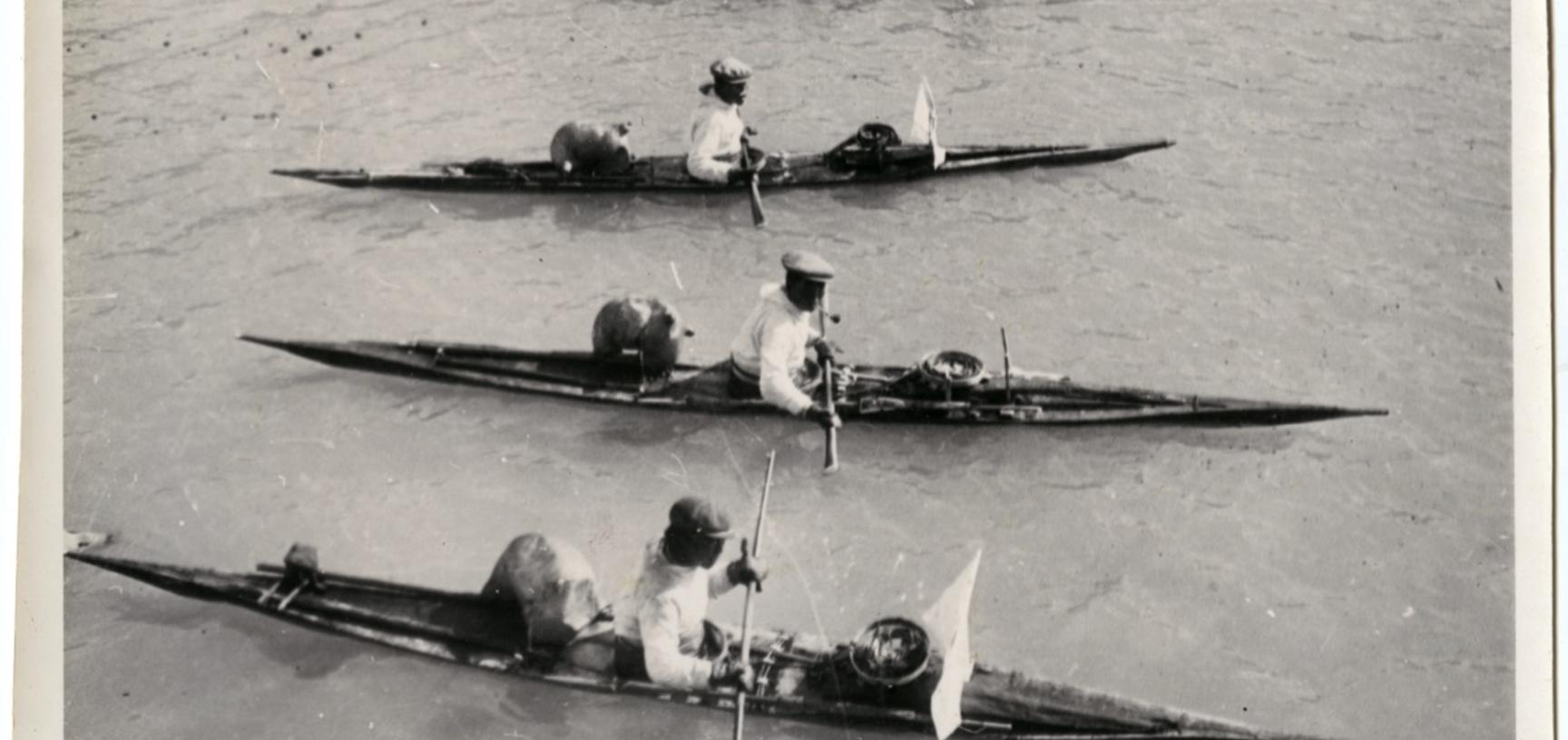 The white screens at the front of the kayaks were used to help disguise the hunters from unsuspecting seals in the water. Photograph by Henry Iliffe Cozens. Greenland. 1930–1931.