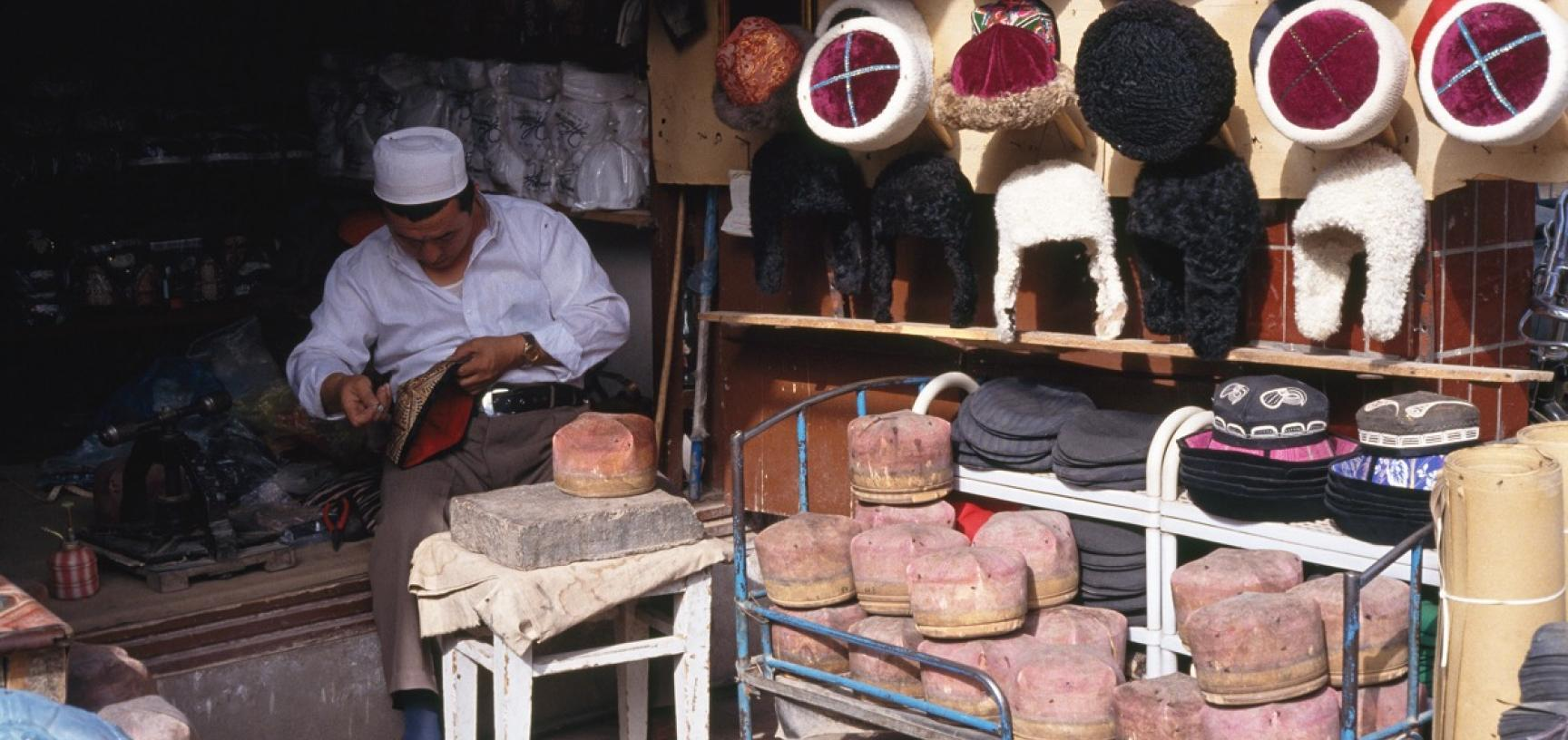 A hat-maker's shop in Kashgar, with various local styles of hat being offered for sale, and hat-moulds stacked on a bed-frame in the foreground. Photograph by Sheila Paine. Kashgar, Xinjiang, China. 1994. (Copyright Pitt Rivers Museum, University of Oxfor