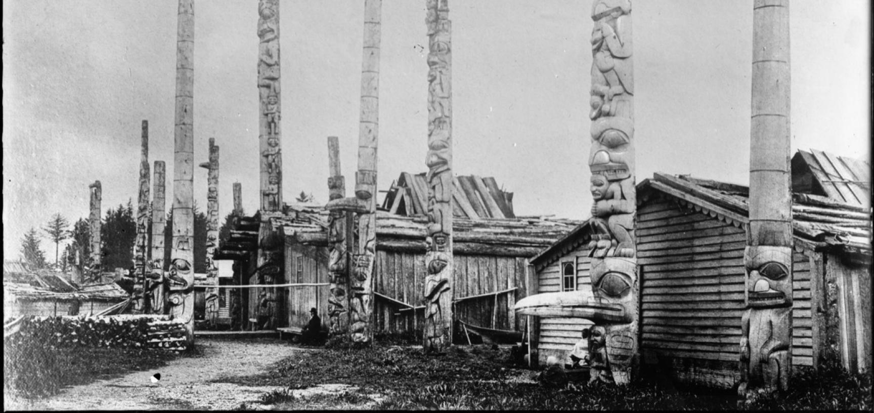 View of houses and totem poles at Masset village, with the frontal post of Star House in the foreground, now located in the Pitt Rivers Museum. Photograph by Bertram Buxton. Masset, Haida Gwaii, Canada. 1882. (Copyright Pitt Rivers Museum, University of O