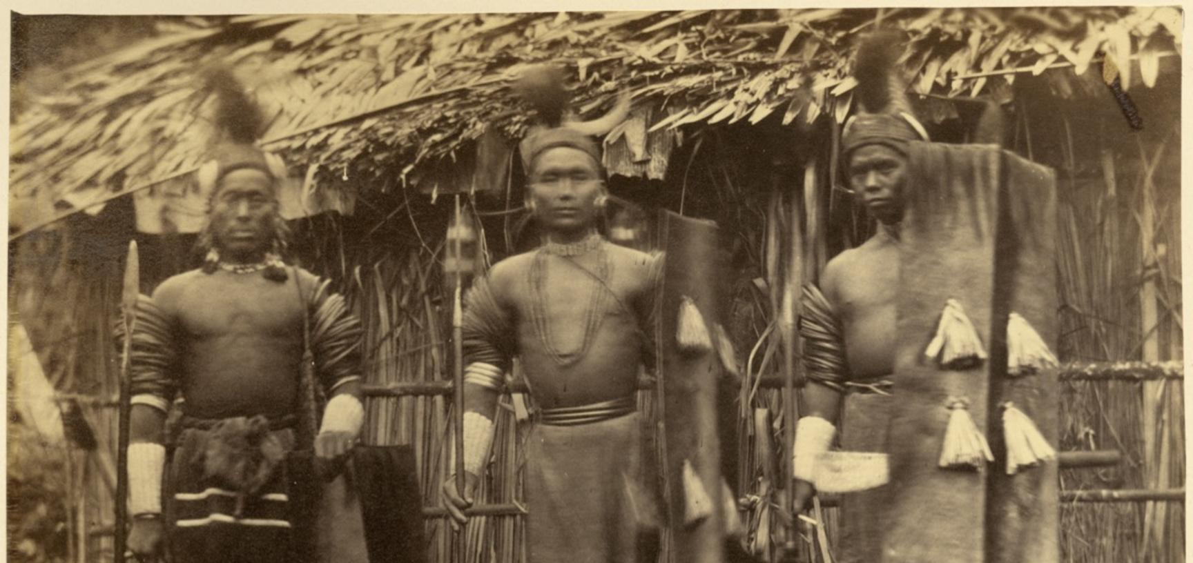'Konyak Nagas' (handwritten caption). Group portrait of three Konyak Naga men, pictured standing, each holding a shield and a weapon (spear or dao). Photographer unknown. Naga Hills District of Assam (now in Nagaland), India. 1873–1874. (Copyright Pitt Ri