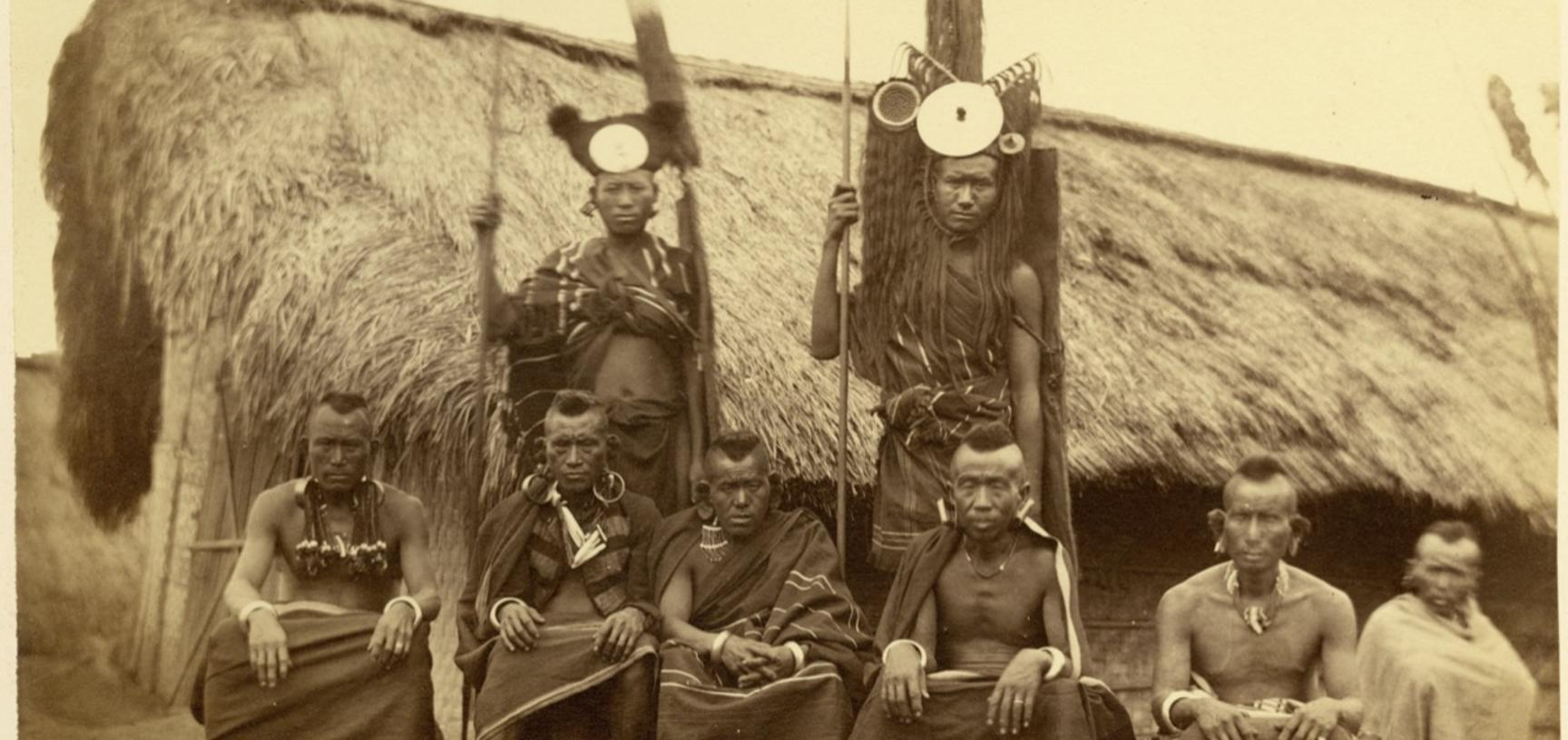 'Tangkhul Nagas' (handwritten caption). Group portrait of Tangkhul Naga men, standing and sitting, pictured in front of a building. Photographer unknown. Naga Hills District of Assam (now in Manipur), India. 1873–1874.