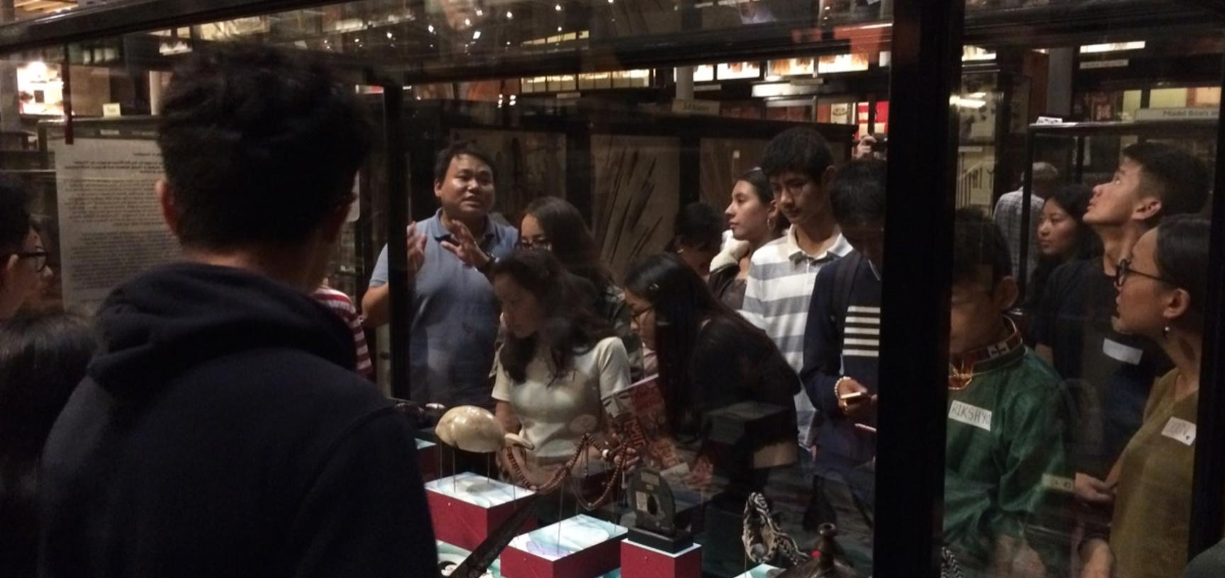Thupten Kelsang discussing the display with teenage members of the UK's Tibetan community during a public engagement event, 'My Tibet Museum', held at the Pitt Rivers Museum in October 2018.