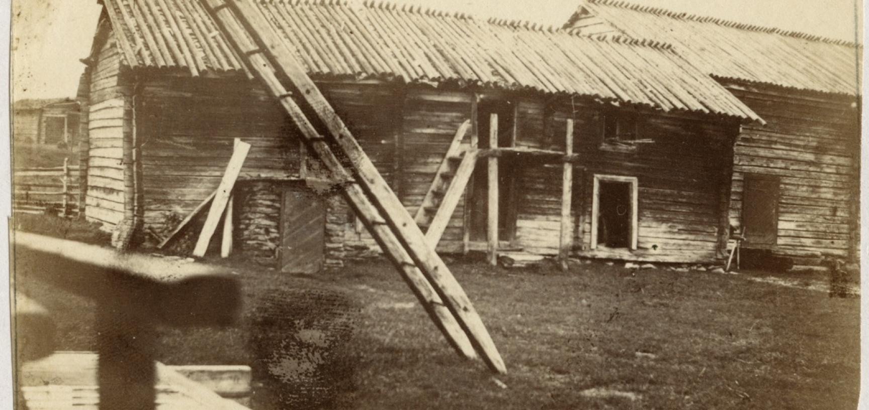 View of buildings at Sodankylä, captioned 'Finnish homestead', showing a storehouse for fuel and loft containing winter clothing, etc. 'One of the peculiarities of Sodankylä is that, though it is a small village collectively, to see it all you have to do