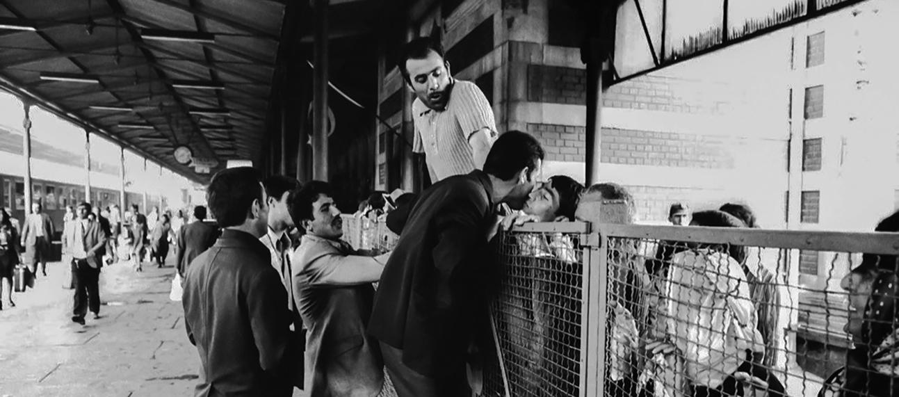 Immigrants divided by a barrier greet and kiss each other at the train station