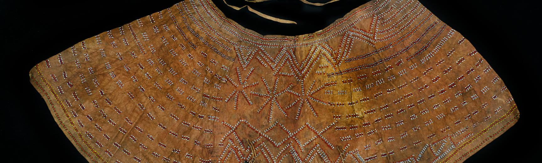 Beaded hide skirt. Donated by Elizabeth Porter. An Iraqw woman visited Elizabeth at her home near Karatu, in northern Tanzania, to ask if she would like to have a skirt made for her. This was after the donor witnessed such a skirt being worn by young wome