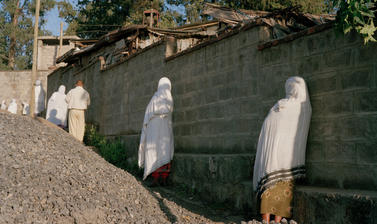 People stop their activities during the midday service for Emperor Haile Selassie. Addis Ababa, Ethiopia. Photograph by Peter Marlow. 2000.