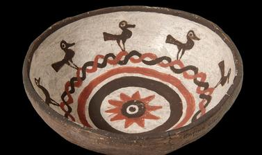 Small eating bowl made in Zuni Pueblo with painted decoration of birds and a sunflower in the centre, collected by James Stevenson for the United States Geological Survey.