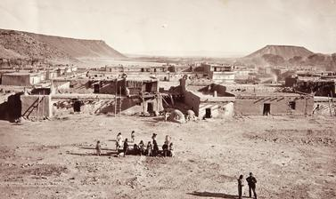 View of houses around the main plaza of San Felipe Pueblo, with the Rio Grande river visible in the distance.