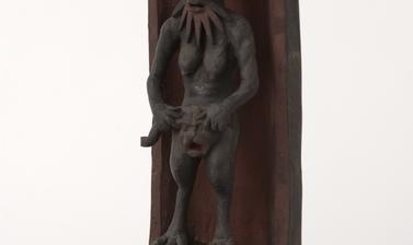 Small statue of a human-type figure with a beard, breasts, bird-like legs.