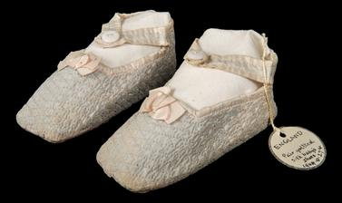 A pair of quilted baby shoes in light blue with delicate pink bows.
