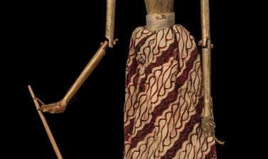 Wooden puppet with white face, body and hair painted gold, with long skirt of red and brown patterned cloth.