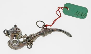 Tiny and intricate silver amulet representing a smoking pipe.