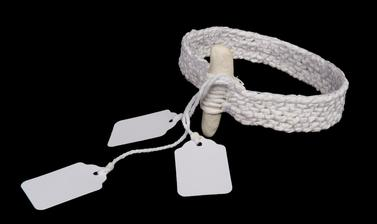Arm band made from woven white material with small white parcel tags attached.
