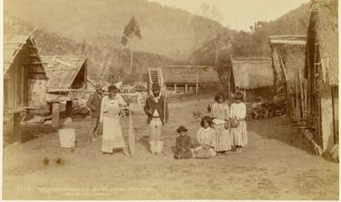 Māori family pictured amidst houses at Pipiriki, a settlement on the Whanganui River. Photograph by Alfred Burton for the Burton Brothers studio (Dunedin). Pipiriki, North Island, New Zealand. 11 May 1885.