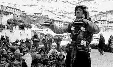 Gatuk Sonam, head Buchen from Mud, performs a stone breaking ceremony on top of a house in Lhalung. Photograph by Patrick Sutherland. Lhalung, Spiti, Himachal Pradesh, India. 2006.
