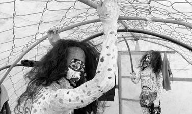 Two Buchen dressed as servants of the Lord of Death keep warm in a polytunnel before a performance. Photograph by Patrick Sutherland. Langsa, Spiti, Himachal Pradesh, India. 2007.