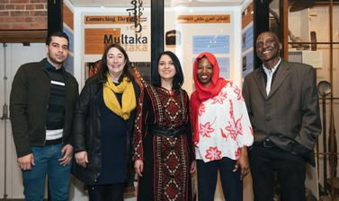 Multaka-Oxford volunteers, and co-curators of the 'Connecting Threads' exhibition, pictured in front of the display case.