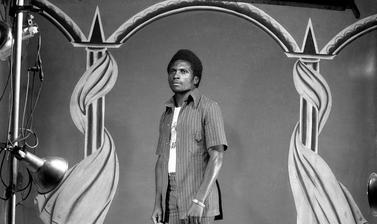 Man dressed in contemporary fashion standing in front of Touselle's third painted backdrop of pillars draped with curtains. Photograph by Jacques Touselle. Mbouda, Cameroon. About 1975.