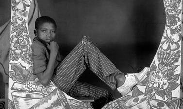 Boy sitting with a painted studio prop: 'Bonne Année Studio Photo Jacques'. Photograph by Jacques Touselle. Mbouda, Cameroon. About 1975.
