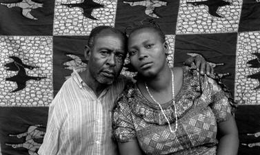 Couple posing in front of a printed cloth backdrop, probably for a marriage certificate photograph. Photograph by Jacques Touselle. Mbouda, Cameroon. 1987.