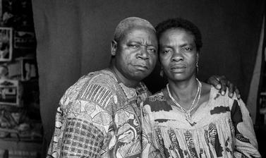 Couple posed for a marriage certificate portrait, with prints on the studio wall visible behind the cloth backdrop. Photograph by Jacques Touselle. Mbouda, Cameroon. Early 1970s.