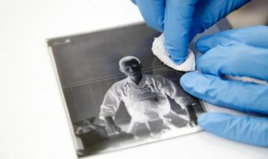 Cleaning a fragile glass negative. (Copyright RD3 Project/Rikuzentakata City Museum)