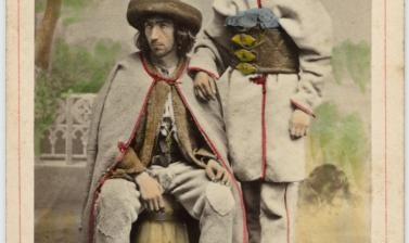 Hand-coloured studio portrait of two Polish men, one sitting, one standing, pictured in front of a painted backdrop. Photograph by the Ignacy Krieger studio. Krakow, Poland. Circa 1870. (Copyright Pitt Rivers Museum, University of Oxford. Accession Number