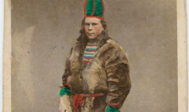 Hand-coloured studio portrait of a Saami man, standing, wearing an animal skin jacket and a distinctive hat, identified in a handwritten note as being from Luleå, Sweden. Photograph by the Rosalie Sjöman studio. Stockholm, Sweden. Circa 1870s. (Copyright