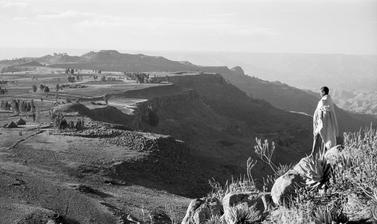 View of an escarpment near Magdala, with a boy standing on rocks in the foreground. Tanta, Ethiopia. Photograph by Wilfred Thesiger. 1960.
