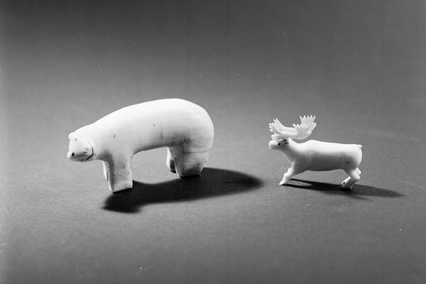 Small carved figure of a polar bear standing on four paws and looking to one side placed to the left of a caribou figure also standing on four legs and facing forwards with a fine set of antlers.