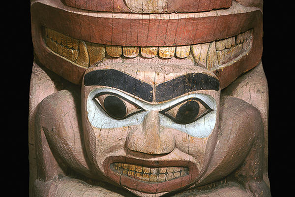 Section of totem pole showing a stylised bear's face above a man's face.