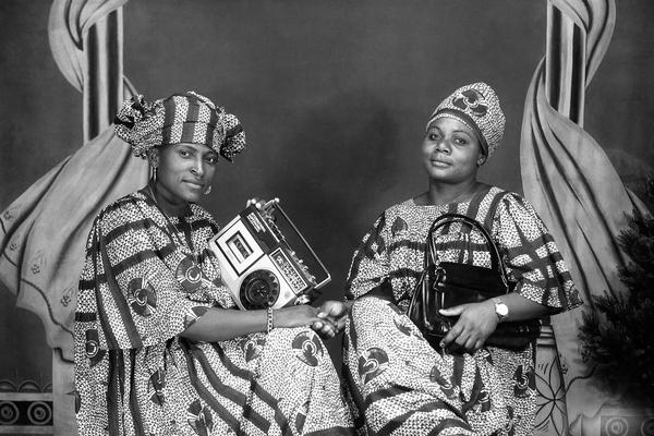 Portrait of two friends holding a cassette player and a handbag, possibly commemorating their purchase of these valued consumer goods. Photograph by Jacques Touselle. Mbouda, Cameroon. About 1975.