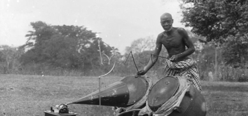 Asante man playing Ntumpane with gramophone in foreground