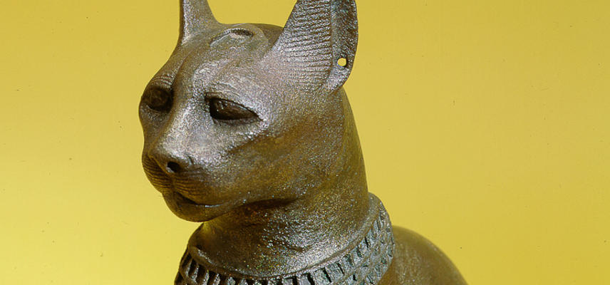Large bronze seated cat with inlaid collar and pendant, mounted on a wooden stand, representing the goddess Bast.