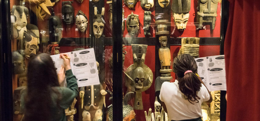 Two pupils stand in front of a glass case full of West African masks.