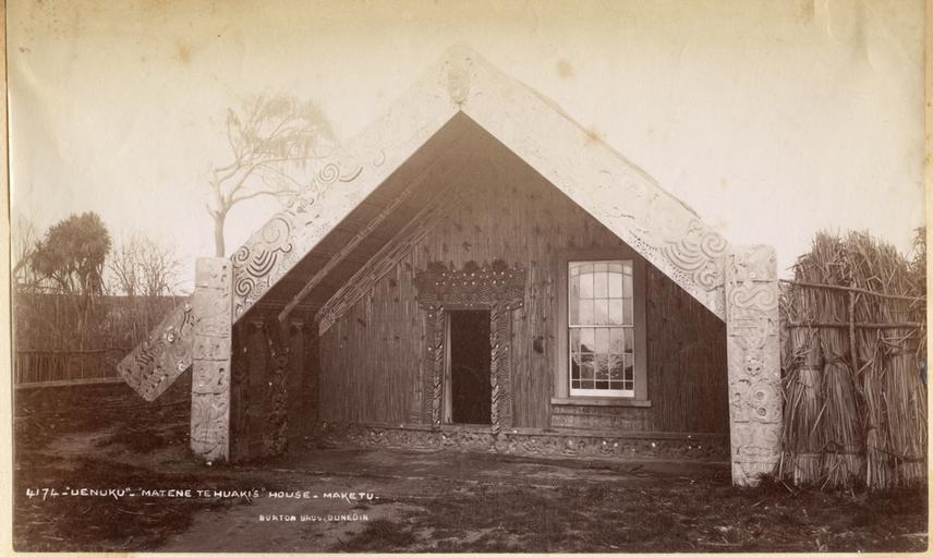 Māori house (whare) with carved and painted wooden decoration. Photograph by Alfred Burton for the Burton Brothers studio (Dunedin). North Island, New Zealand. Circa 1887.