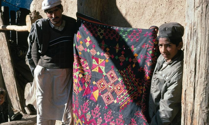 A man and boy holding an embroidered textile typical of the Palas valley in Kohistan district of north-western Pakistan. Photograph by Sheila Paine. Sherakot, Khyber Pakhtunkhwa, Pakistan. 1993.